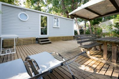 Komfortables Mobilhaus mit Liegestühlen in der Sonne auf einem Campingplatz